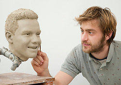 """© Licensed to London News Pictures. 19/02/2013. London, UK Sculptor Alex Carlisle works on the clay head of Liam Payne. Madame Tussauds today released pictures of sculptors working on the life-like clay heads of the five members of pop band """"One Direction ' The clay heads will be used to create the moulds for their new wax figures. Niall, Liam, Louis, Harry and Zayn have been closely involved in the creation process giving the creative team two sittings at which hundreds of measurements were taken to ensure total accuracy. The clay heads will now be used to make the moulds for the final wax figures, which will be revealed in London. Photo credit : Madame Tussauds /LNP"""