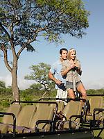 Couple on safari standing in jeep woman holding binoculars