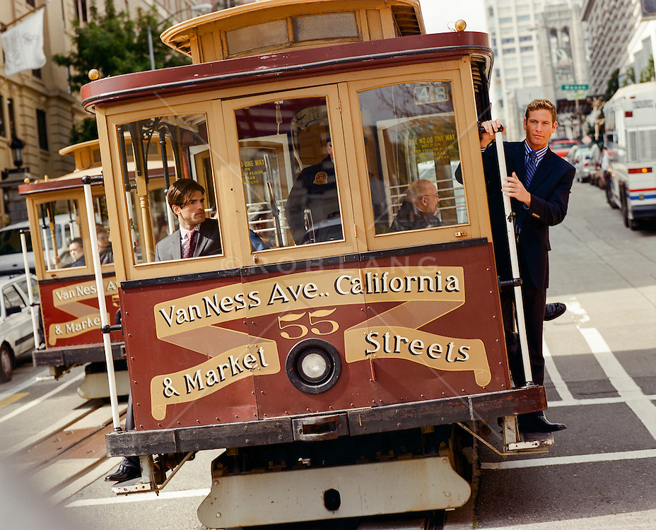 businessman riding on a cable car in San Francisco, CA