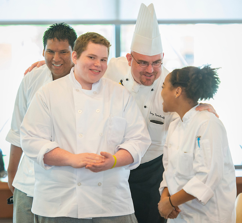 Westside High School students Santiago Castaneda, Andrew Winkle and Barrosha Boykin are congratulated by Aramark chef Gerry UpdeGraff after being named the top team in the Cooking for Change challenge at Rice University, April 12, 2014.