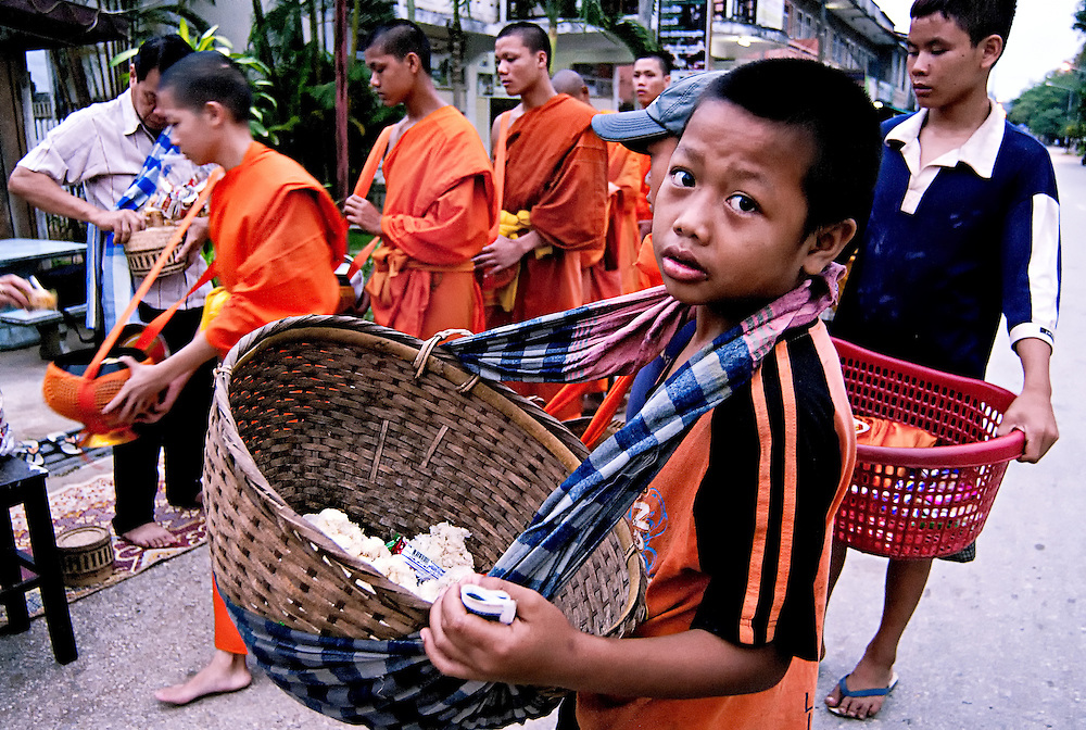 Buddhist monks walking the streets of Luang Prabang early in the morning collecting alms and passing on excess to poor children.