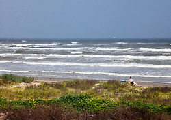 Dunes, girl, waves, and beach equate with Galveston on the Texas Gulf Coast.