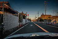 National Route 6, which runs north to south through the nuclear no-entry zone, past Fukushima Daiichi Nuclear Power Plant, was opened to through traffic in September 2014, but access to the towns in the nuclear no-entry zone remain off-limits.  Route 6 narrows through Kumamachi in Okuma, less than 3km (1.9 miles) from Fukushima Daiichi Nuclear Power Plant.  Stopping of cars is forbid and gates prevent vehicles and people from leaving the highway.  Fukushima Prefecture, Japan.