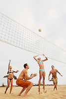 Woman Jumping for Volleyball During Game on Beach