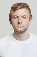 Portrait of serious young man in t-shirt against gray background