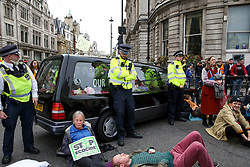 © Licensed to London News Pictures. 07/10/2019. London, UK.  Police officers guard a hearse at the roundabout in Trafalgar Square as environmental and climate change activists from the Extinction Rebellion group protest in Westminster, calling for the UK Government to take responsibility and enact immediate, profound and sweeping changes to address the crisis on climate and ecological changes. Photo credit: Dinendra Haria/LNP