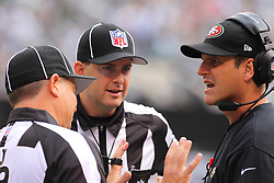 Sept 30, 2012; East Rutherford, NJ, USA; San Francisco 49ers head coach Jim Harbaugh talks to head linesman John McGrath (5) and referee Scott Green (19) during the first half at MetLIfe Stadium.