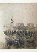 man doing a handstand on the walls of the castle tower at Foix France 1880s