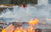 A protester watches as structures at the Oceti Camp at Standing Rock are burned before their two p.m. deadline to vacate the camp. (For The New York Times)
