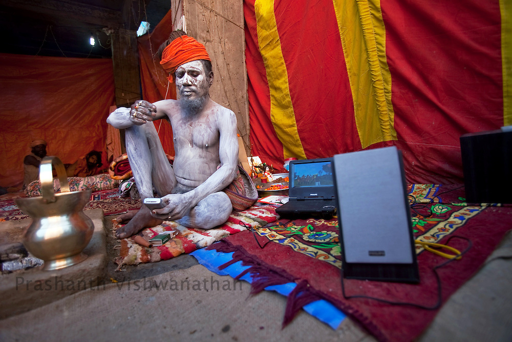 A naked Naga sadhu texts on his phone as his dvd player plays spiritual songs on portable speakers during the Maha Kumbh ceremony in Haridwar, February 11, 2010.  Photographer:Prashanth Vishwanathan