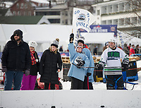 Ryan Turmel raises the team Bumbles flag surrounded by friends and family in support of their team during their final round game with the Frozen Hacks during Sunday's New England Pond Hockey Classic.  (Karen Bobotas/for the Laconia Daily Sun)
