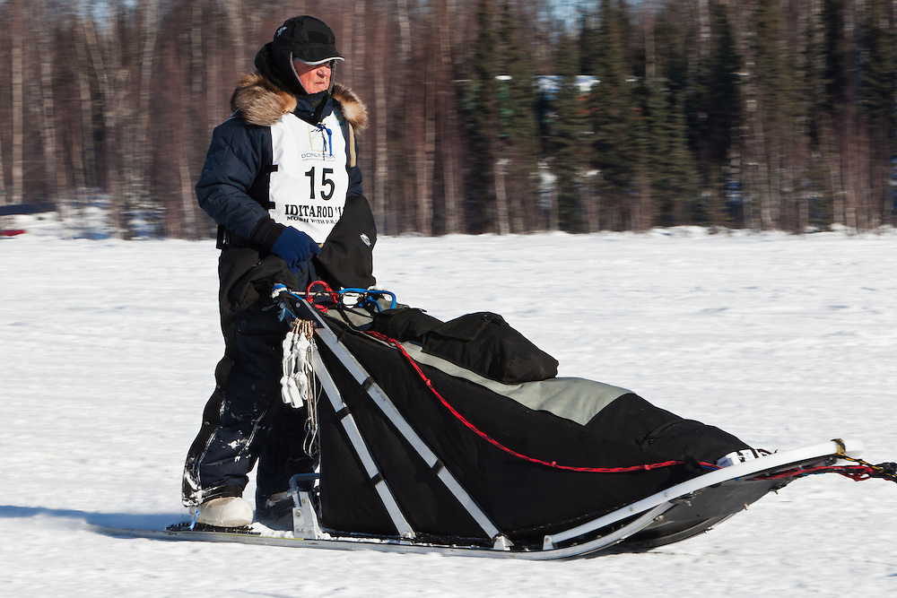 Musher Bob Storey competing in the 39th Iditarod Trail Sled Dog Race on Long Lake after leaving the Willow Lake area at the restart in Southcentral Alaska.  Afternoon.
