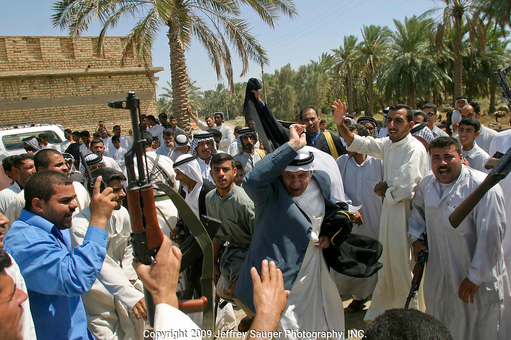 Malik Al-kasid, center in gray suit coat, and his son Emad Al-kasid, behind him in gold and black, participate in Hawaies, a traditional tribal Arabic dance, at the Al-kasid family's Istikbal, or homecoming, in their home village of Suq ash Shuyukh about 20 miles southeast of Nasiriyah, Iraq, Tuesday, July 29, 2003. ..When Malik Al-kasid's caravan approached, guns were fired to announce his family's arrival. The welcming party then, returns fire to welcome him. The two parties move toward each other dancing and shooting until they join in the middle where the Hawaies occurs. ..The Al-kasid family fled Iraq after the Gulf War and their part in the uprising against Saddam Hussein in 1991, spent 3 years in Rafa, Saudi Arabia and finally settled in Dearborn, MI. The family hasn't been home to Iraq in 13 years.