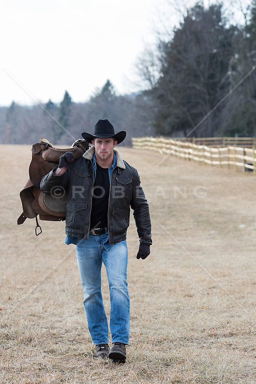 All American rugged cowboy with a saddle over his shoulder on a ranch
