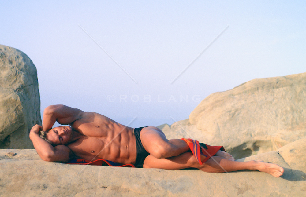 male bodybuilder reclining on rock formations in Southern California