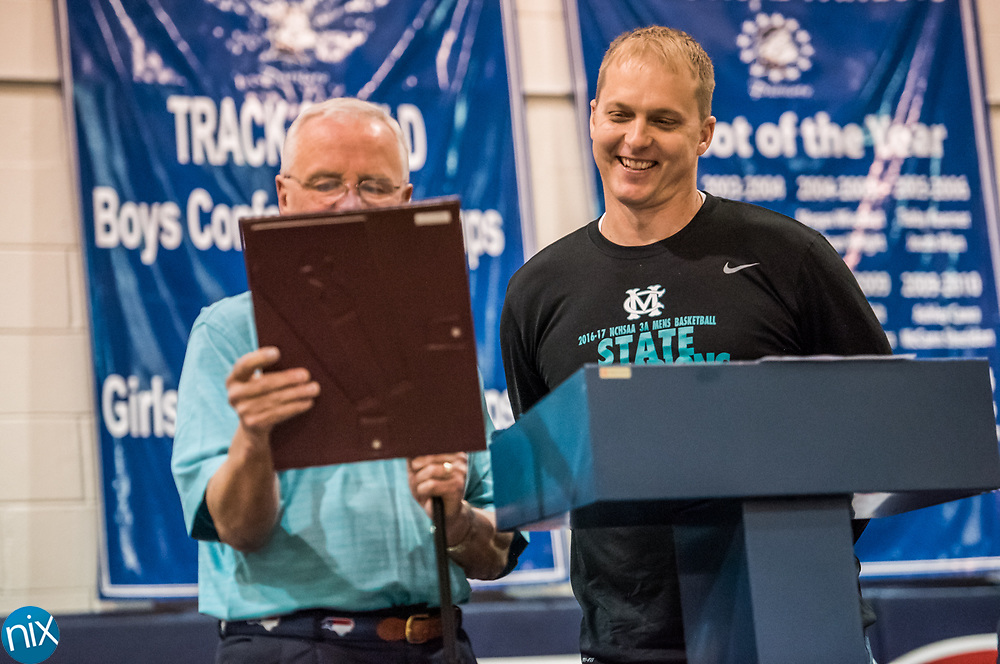 Cox Mill head coach Jody Barbee laughs as Concord Mayor Scott Padgett reads a proclamation from the city honoring the basketball team as they celebrate the 3A Basketball State Championship during a rally at Harris Road Middle School Thursday afternoon.