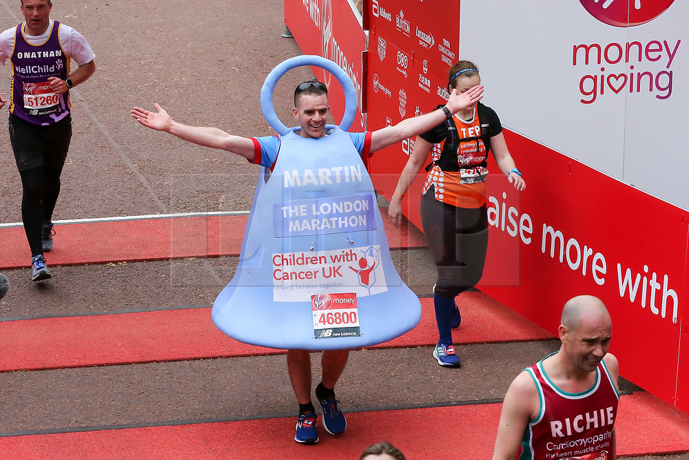 © Licensed to London News Pictures. 28/04/2019. London, UK. A man dressed in a bell at the finish of 2019 Virgin Money London Marathon. Photo credit: Dinendra Haria/LNP