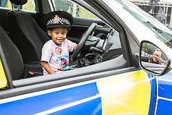 © Licensed to London News Pictures . 12/08/2018. Manchester , UK . NYLAH RICHINGS (three, from Radcliffe) in a police car and PC PHIL INGHAM , Neighbourhood Police Officer for Moss Side , seen in the wing mirror , at the event . The second day of the annual Caribbean Carnival in Alexandra Park in Moss Side , celebrating music , food and Afro-Caribbean culture . A nearby shooting overnight lead to at least ten people injured . Ten people are in hospital . Photo credit : Joel Goodman/LNP