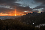 Last week this spectacular sunrise filled the eastern sky as seen from an overlook in the Bighorn Mountains. Even before the sun made it over the horizon, a pillar of light was shining above the sun, appearing like a flame. While sun pillars aren't that uncommon, it is rare for them to be as tall as this one. This optical phenomenon is caused by the collective glint of millions of flat hexagonal ice crystals slowly falling through the air. When they are aligned just right at sunrise or sunset, it forms a light pillar. Pillars can form above other bright light sources as well such as the moon and even streetlights when the air is cold enough.