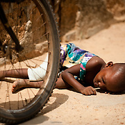 A child asleep on a footpath on 6 March 2010, likely ill with malaria.