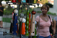 Woman admires artistic wooden pepper grinders for sale in artist's booth at the St. Louis Art Fair in Clayton, Missouri.