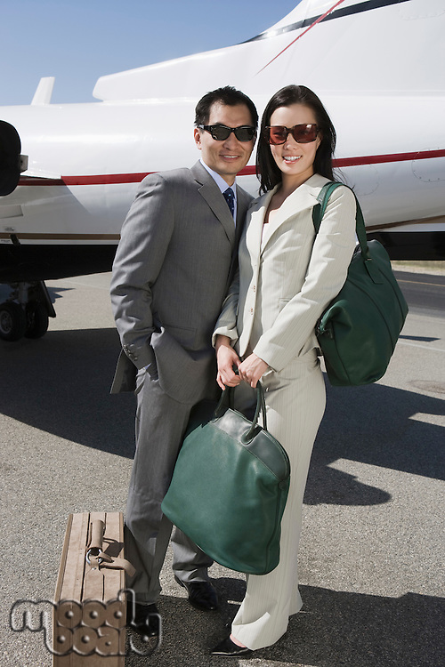 Portrait of mid-adult Asian business couple standing outside of private airplane.