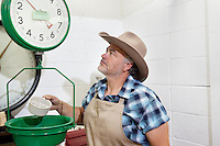 Mature cowboy looking up at weight scale