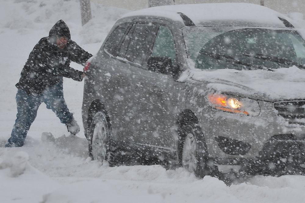 Good Samaritans help push a stranded motorist stuck in deep snow on Stefko Boulevard Thursday, February 13, 2013 in Bethlehem, PA.