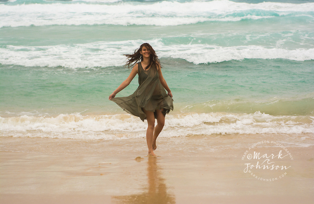 Young woman on the beach on a stormy day, N. Stradbroke Island, Queensland, Australia