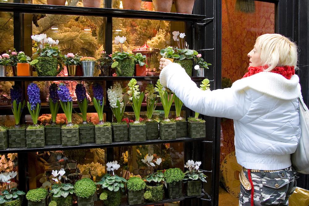 Woman visits florist shop and chooses plant near Boulevard Saint Germain, Latin Quarter, Paris, France