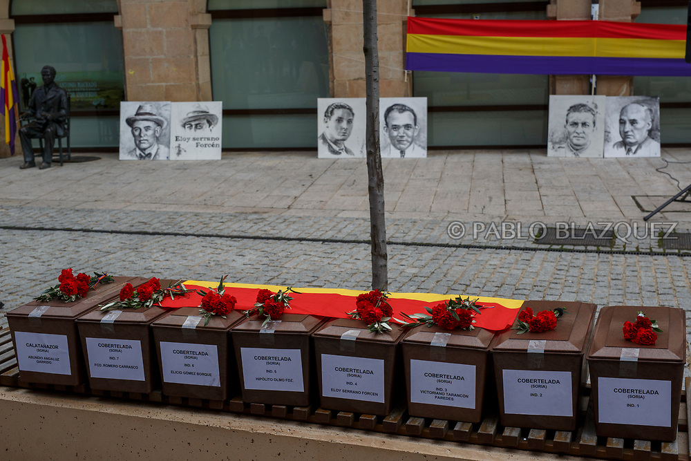 14/04/2018. Coffins containing the bodies of victims of Spain Civil War exhumed in Cobertelada and Calata&ntilde;azor are placed on a bench as portraits depicting Francisco Romero Carrasco (L), Eloy Serrano Forcen (2L), Elicio Gomez (3L), Hipolito Olmo Fernandez (3R), Victoriano Tarancon (2R) and Abundio Andaluz (R) lean against a wall during a homage to hand the remains to their relatives on April 14, 2018 in Soria, Spain. La Asociacion Soriana Recuerdo y Dignidad (ASRD) 'The Soria Association for Memory and Dignity' celebrated a tribute to hand over the remains of civil war victims to their families. The Society of Sciences of ARANZADI helped with the research, exhumation and identification of the bodies, after villagers passed the information about the mass grave, 81 years after the assassination took place, to the ASRD. Seven people were assassinated around August 25, 1936 by Falangists, as part of General Francisco Franco armed forces, and buried in the 'Fosa de los Maestros' (Teachers Mass Grave) near Cobertelada, Soria, after being taken from prison of Almazan during the Spanish Civil War. Five of them were teachers in the region, and also friends of Spanish writer Antonio Machado. The other two still remain unidentified. Another body was assassinated by Falangists accompanied by a priest in 1936, and was exhumed on 23 September of 2017 near Calata&ntilde;azor, Soria. It belonged to Abundio Andaluz, a politician, lawyer and musician in Soria.<br /> Spain's Civil War took the lives of thousands of people on both sides, and civilians. But Franco continued his executions after the war has finished. Teachers, as part of the education sector, were often a target of Franco's forces. Spanish governments has never done anything to help the victims of the Civil War and Franco's dictatorship while there are still thousands of people missing in mass graves around the country. (&copy; Pablo Blazquez)
