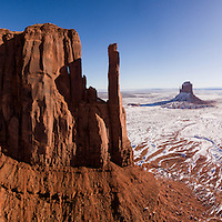 USA, Arizona, Monument Valley Navajo Tribal Park, Aerial panoramic view of winter morning sun lighting snow-covered sandstone mesas at Monument Valley