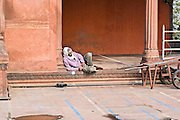 INDIA, OLD DELHI:  East Indian Muslim man resting in the courtyard of the Jama Masjid Mosque in Old Delhi as he waits for prayer time.
