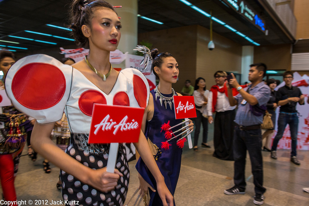 01 OCTOBER 2012 - BANGKOK, THAILAND:  Air Asia employees parade through the terminal during the opening of Air Asia's operations at Don Mueang International Airport in Bangkok Monday. Don Mueang International Airport is the smaller of two international airports serving Bangkok, Thailand. Suvarnabhumi Airport, opened in 2006 is the main one. Don Mueang was officially opened as a Royal Thai Air Force base on 27 March 1914 and commercial flights began in 1924. Don Mueang Airport closed in 2006 following the opening of Bangkok's new Suvarnabhumi Airport, and reopened as a domestic terminal for low cost airlines after renovation on 24 March 2007. Closed during the flooding in 2011, Don Mueang was again renovated and reopened in 2012 as the airport for low cost airlines serving both domestic and international passengers. On Monday, Air Asia, Asia's leading low cost airline, transferred all of their flight operations to Don Mueang and the airport was officially reopened. Suvarnabhumi International Airport is already over capacity and Don Mueang's importance as a hub is expected to grow.   PHOTO BY JACK KURTZ