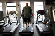 Guest Greg Dybisz walks backwards on a treadmill during a cardio interval class at the Biggest Loser Resort in Ivins, Utah September 7, 2010.  Guests at the resort affiliated with the popular reality television show, some staying for months, workout in an aerobics room, a gym and a swimming pool for 6 to 7 hours each day and are restricted to a daily 1,200 calorie alcohol and caffiene free diet.  REUTERS/Rick Wilking (UNITED STATES)