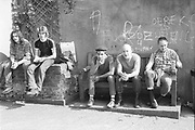 Dom, with friend and Edema, Alf and Walter sat on a wall and bench with graffiti and beer. High Wycombe, UK, 1980s.