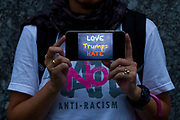 "A Japanese activist holds a smart phone with the message ""Love Trumps Hate"" as she joins other  American and Japanese  people at the  ""Enough is Enough"" rally in Toranomon, Tokyo Japan, Tuesday August 15th 2017. Around 20 people gathered to take part in a global day of action demanding fairer policies in the United States that do not favour only the rich and do not remove human rights from ordinary people. A silent vigil was held for 30 minutes at 6pm so that the voices that could be heard after spoke louder. This is the closest it is possible to protest to the US embassy in Tokyo."