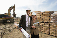 Two architects standing on construction site holding blueprints