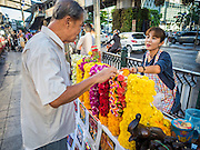 19 AUGUST 2015 - BANGKOK, THAILAND: A man buys a flower garland to leave as an offering on the first day the Erawan Shrine reopened in Bangkok. Erawan Shrine in Bangkok reopened Wednesday morning after more than 20 people were killed and more than 100 injured in a bombing at the shrine Monday, August 17, 2015. The shrine is a popular tourist attraction in the center of Bangkok's high end shopping district and is an important religious site for Thais. No one has claimed responsibility for the bombing.        PHOTO BY JACK KURTZ