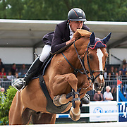 Piet Raijmakers Jr. showing the tension of jumping a fence during Concours Hippique Haarlemmermeer in the Netherlands, while his horse seems quite relaxed with its front legs crossed.
