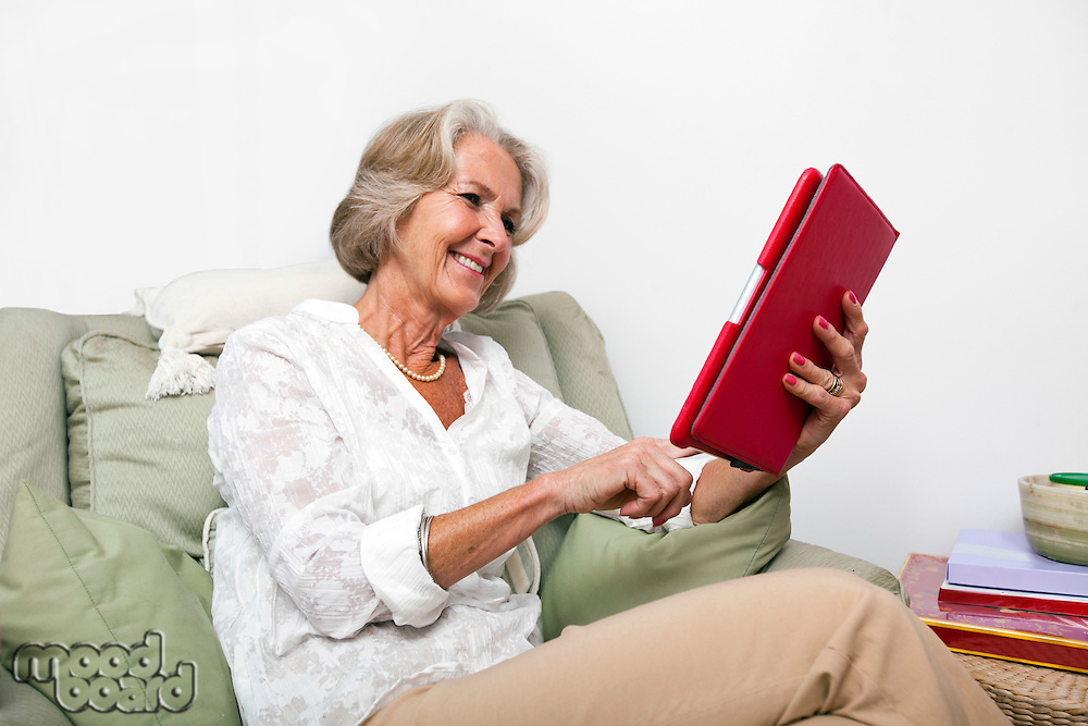 Senior woman using digital tablet on armchair at home