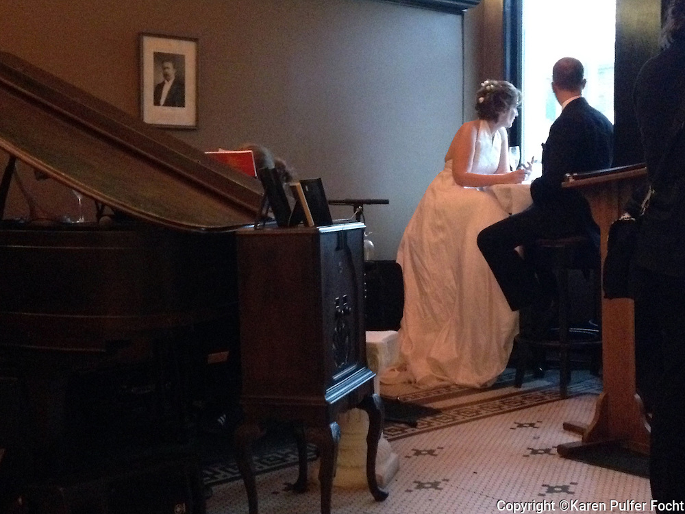 Love on a rainy day. A bridge and groom take respite from the rain at Grawmeyers in downtown Memphis, Tennessee following their wedding ceremony.  Scenes from downtown Memphis, Tennessee.