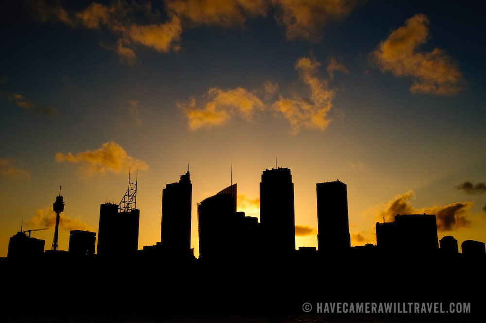 View from Mrs. Macquarie's Point of Sydney's CBD skyline with a golden glow of the setting sun