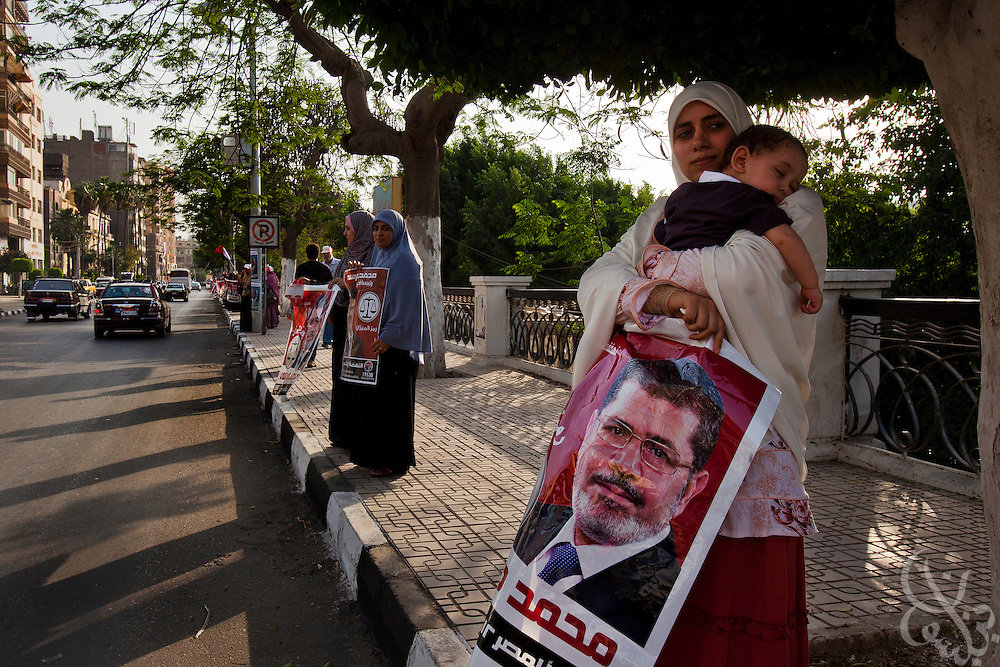 An Egyptian mother holds her sleeping child as she joins other supporters to form a human chain event for Egyptian Islamist presidential candidate Dr. Mohamed Morsy May 17, 2012  in the Nile delta city of Mansoura, Egypt. Morsy, the Muslim Brotherhood's candidate once lagged far behind in the polls, but is now considered a strong underdog candidate because of the legendary organizational machine his group commands during election times. (Photo by Scott Nelson) in Mansoura, Egypt.