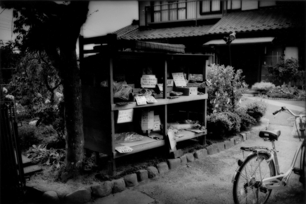 A common sight in rural Japan: Self-service produce sale by the honor method at a Japanese farmhouse completely swallowed up by residential development in a western Tokyo suburb, Naganuma, Tokyo, Japan.  Customers are expected to pay for produce laid out by trusting farm families.  No one is present to make sure money is left for the vegetables taken.