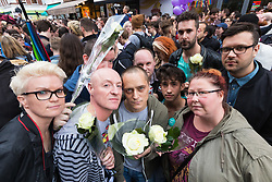 Old Compton Street, Soho, London, June 13th 2016. Thousands of LGBT people and their friends converge on Old Compton Street in London's Soho to remember the fifty lives lost in the attack on gay bar Pulse in Orlando, Florida. PICTURED: Carrying single white roses, a group of friends pose for the camera.
