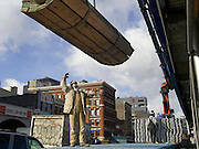 worker giving directions while hoisting wood on to a building under construction