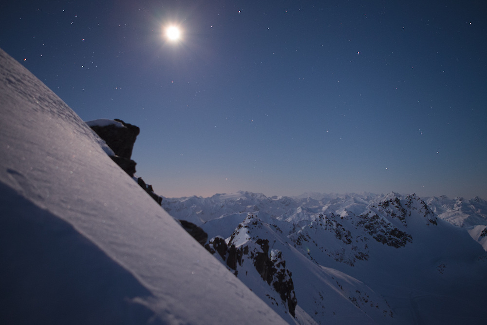 The moon and stars shine over the mountains in Andermatt, Swiss Alps