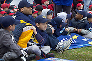 Middletown, New York - Young baseball players and their coaches sit on the field after marching in the 60th annual Middletown Little League parade on April 14, 2013.