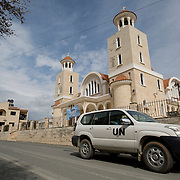 A United Nations patrol drives past a church with the town mosque visible at the far left in the village of Pyla in the Larnaca District of Cyprus March 11, 2014.  Pyla is one of only four villages located within the United Nations Buffer Zone and is a mixed community with both Greek and Turkish Cypriots living side by side. This year marks 40 years since the Cyprus National Guard staged a coup in Cyprus and the subsequent Turkish military intervention, which escalated a civil war between the Greek and Turkish Cypriot communities on the island. After the ceasefire a heavily restricted UN controlled Buffer Zone between the north and south of the island was put into operation. It stretches 180 Km across the whole island measuring 7.4 km at its widest and 3.3 meters at its narrowest point. It is restricted to the general public and no Greek or Turkish Cypriots are allowed inside. REUTERS/Neil Hall (BRITAIN)